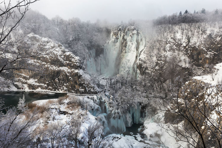 Scenic view of waterfall in forest during winter