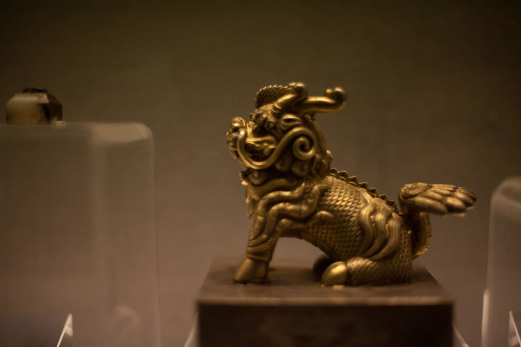 Small gilded animal statue against wall