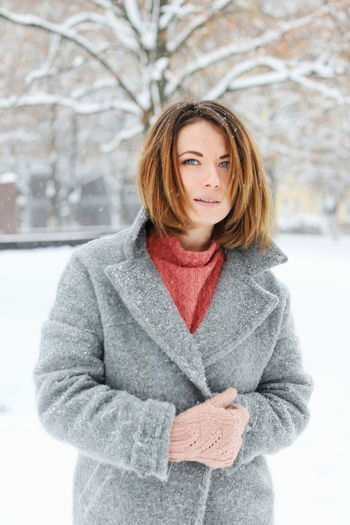Portrait Of Young Woman Standing On Snow Covered Field
