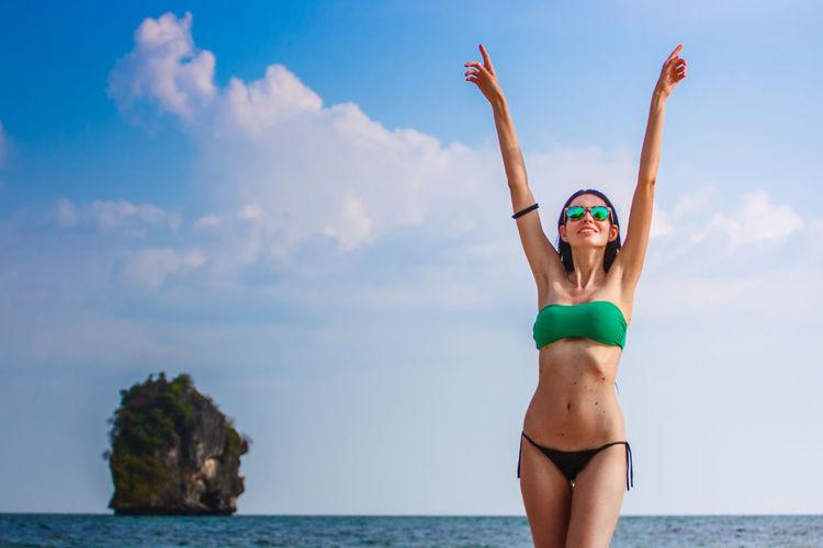 Carefree woman wearing bikini standing at beach against sky