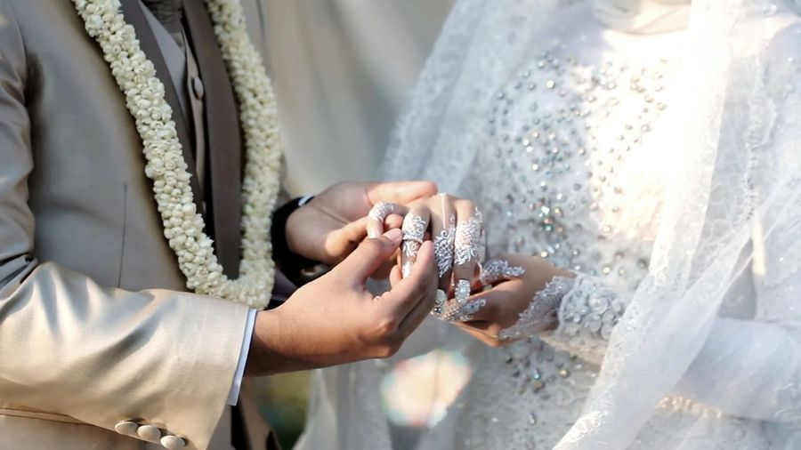 Midsection of bridegroom wearing wedding ring to bride in wedding ceremony