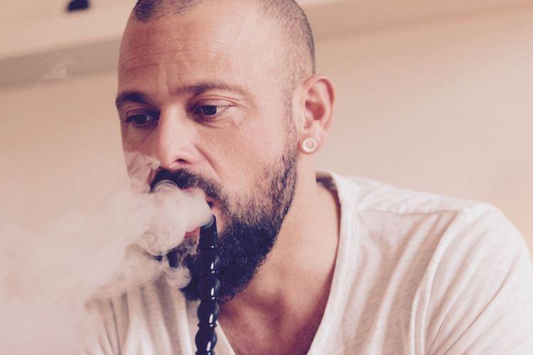 Portrait of man smoking water pipe