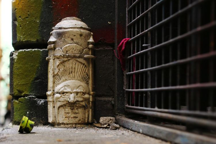 Sculpture against abandoned wall