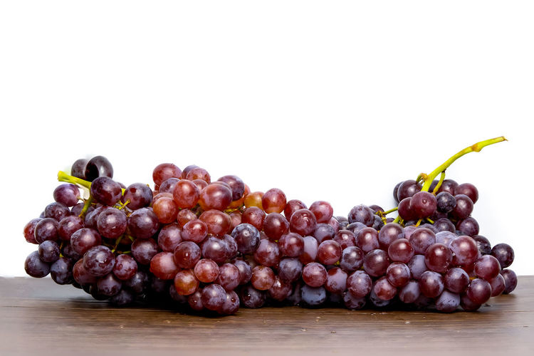 Close-up of grapes on table against white background