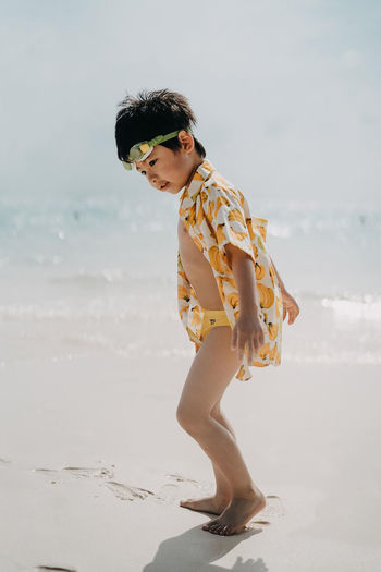 Side view of boy walking at beach