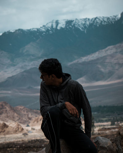 Man sitting on land against mountains