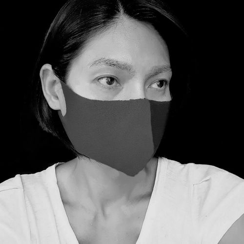 Woman wearing mask looking away against black background