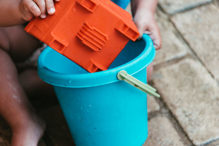 Low section of boy playing with bucket while sitting outdoors