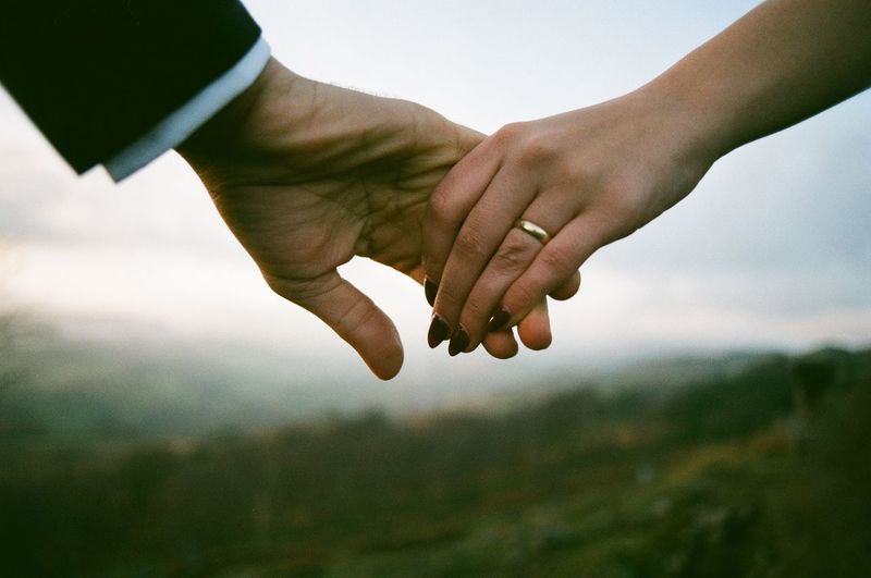 Cropped image of couple holding hands against sky