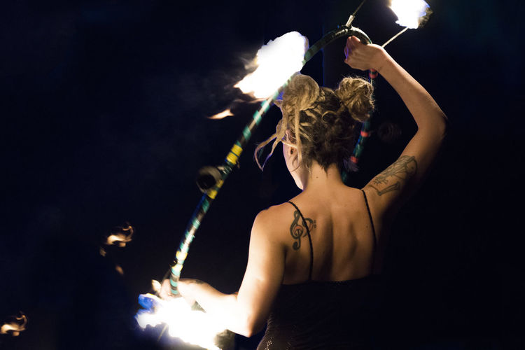 Woman holding burning ring while performing at night