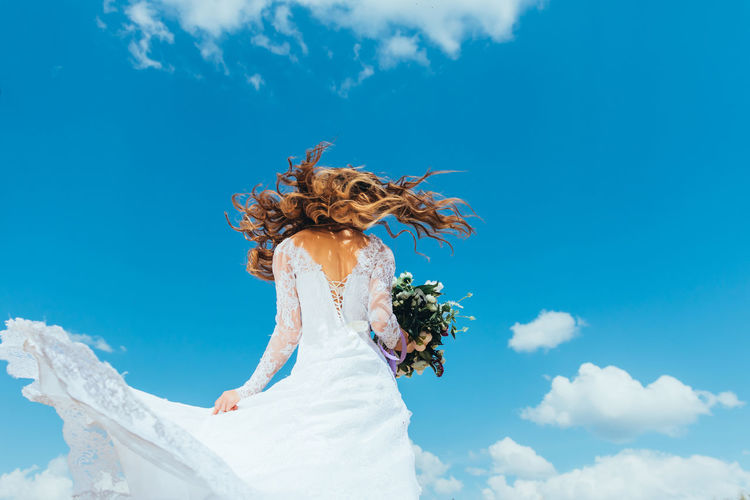 Low Angle View Of Woman With Bouquet Standing Against Sky