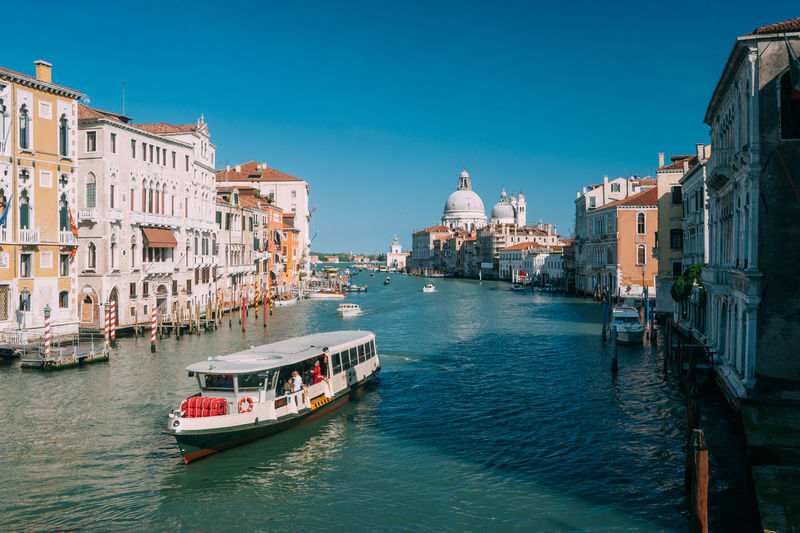 Ferry Moving In Grand Canal With Santa Maria Della Salute In Background