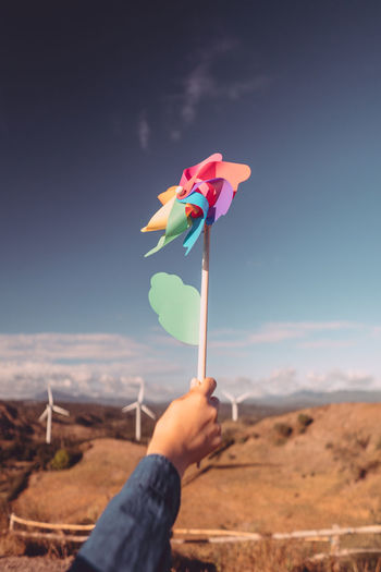 Cropped had of person holding pinwheel toy against sky