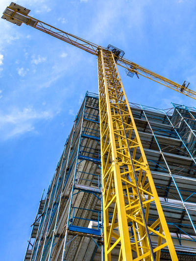 Construction Crane Building Architecture Under Industry Sky Site Concrete Business Development City Urban House Work Structure Engineering Build Blue Equipment Steel High New Modern Industrial Estate Tall Home Skyscraper Tower Apartment Cement Frame Housing Scaffolding Exterior Project Property Block Metal Technology Residential  Built Yellow