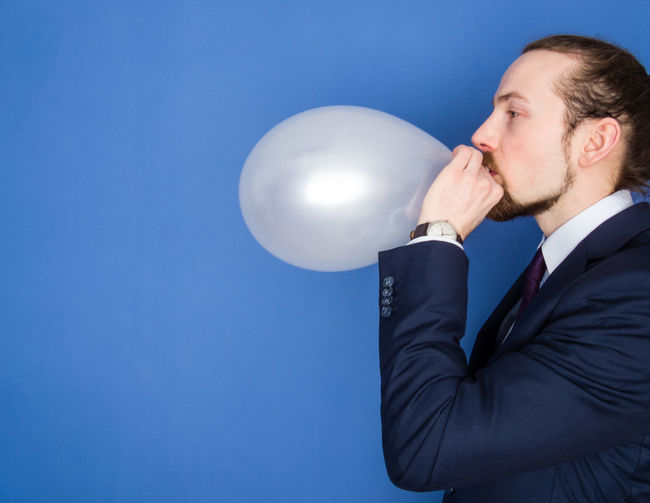 Young handsome bearded man in a suit blowing up a white balloon. Blue background. Balloon Beard Blowing Up Balloon Blue Business Business Finance And Industry Businessman Carefree Confidence  Economy Elegant Flower Helium Balloon Holding Man Manager One Person Party Person Relax Self Portrait Suit Well-dressed Young Adult