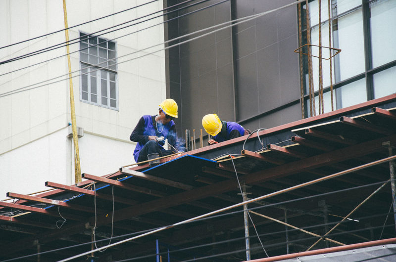 Low angle view of people working on building