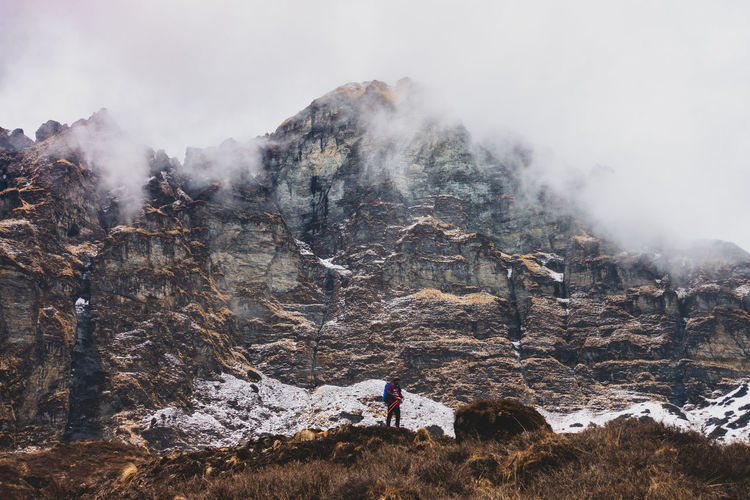 Man standing against mountain during foggy weather