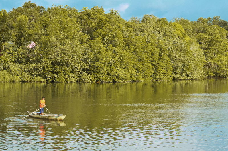 Mid adult man standing in boat on lake against trees