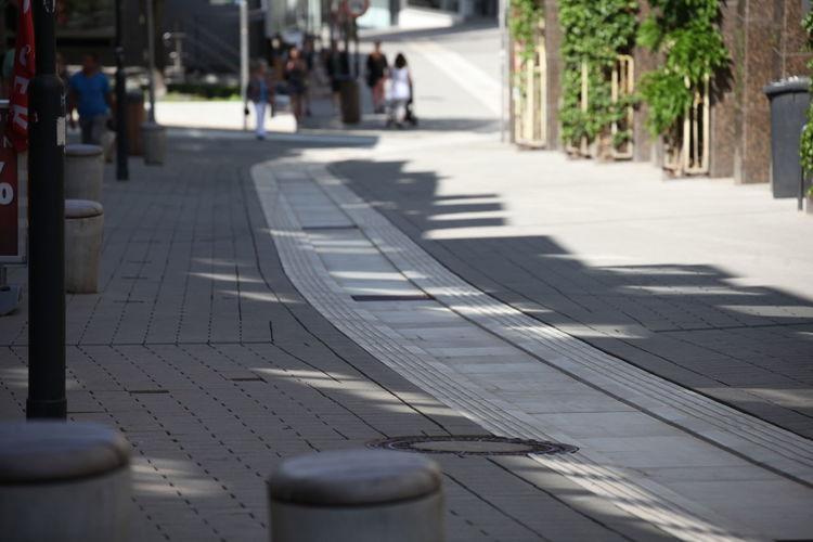 Footpath by sidewalk in city