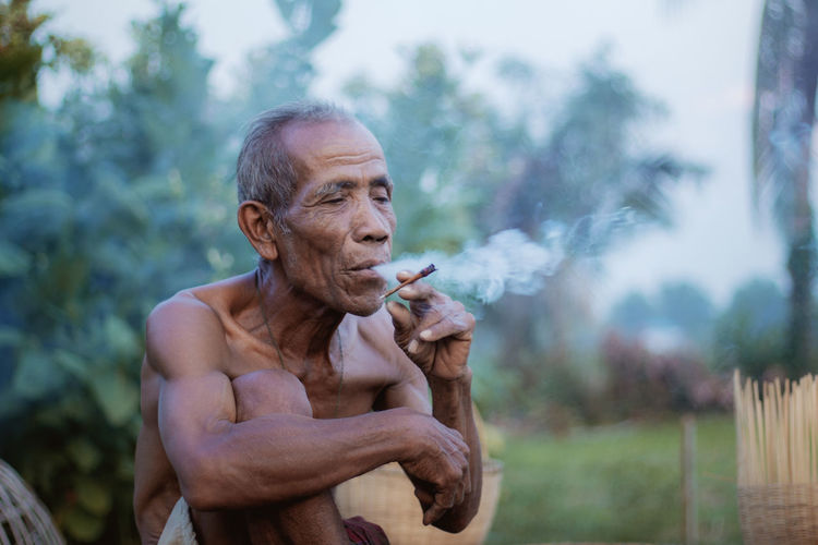 One Person Lifestyles Shirtless Adult Smoking - Activity Senior Adult Smoking Issues Social Issues Bad Habit Focus On Foreground Males  Day Men Cigarette  Leisure Activity Smoke - Physical Structure Real People Outdoors