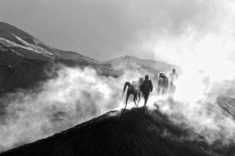 Silhouette man riding horse on mountain against sky