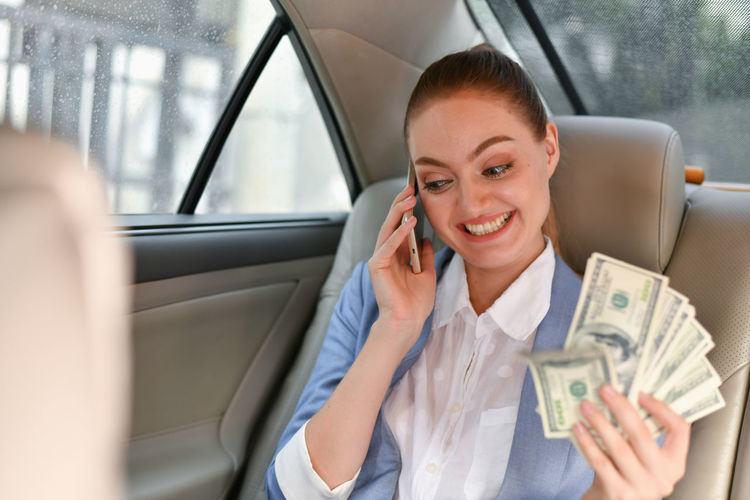 Smiling Businesswoman With Paper Currency Talking On Phone While Sitting In Car