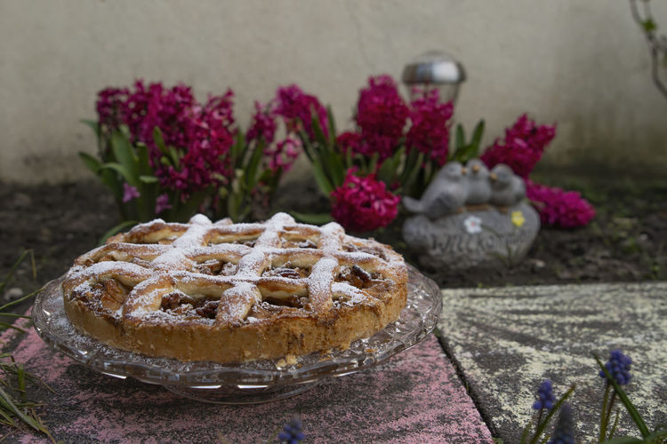 Apple pie on ground and red flowers