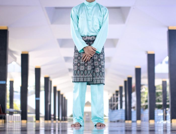 Low section of man in traditional clothing standing under bridge