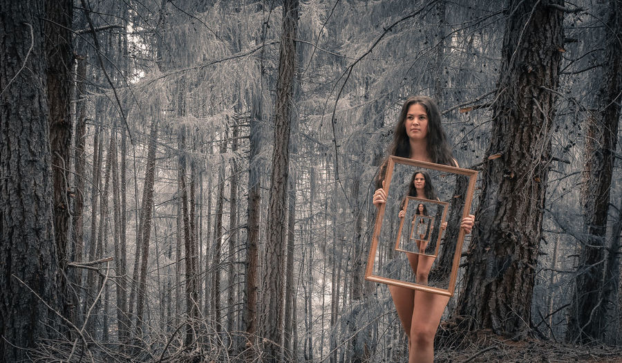 Woman Holding Mirrors While Standing Against Trees In Forest