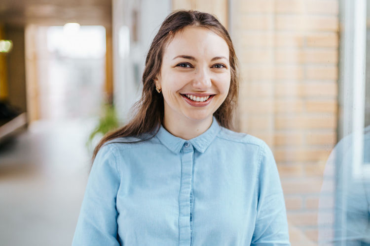 cheerful businesswoman wearing a blue blouse Smiling Portrait Happiness One Person Confidence  Business Person Headshot Looking At Camera Emotion Adult Young Adult Office Indoors  Business Focus On Foreground Front View Brown Hair Casual Clothing Teeth Hair Beautiful Woman Hairstyle Brunette Cheerful Caucasian