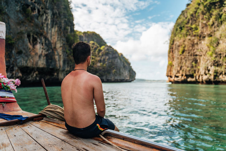 Rear view of shirtless man sitting on boat