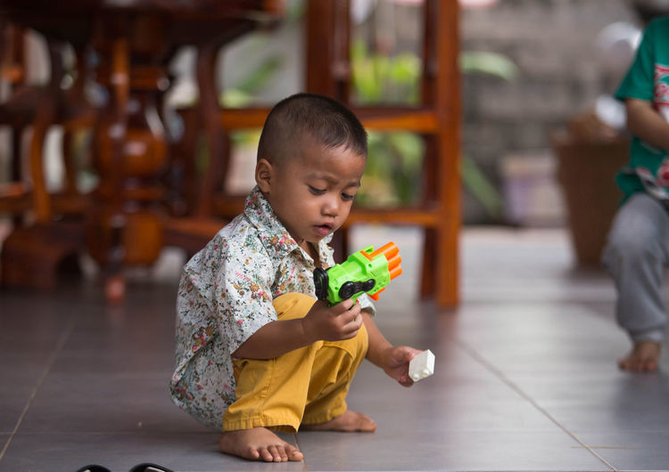 Cute boy holding toy while sitting on floor