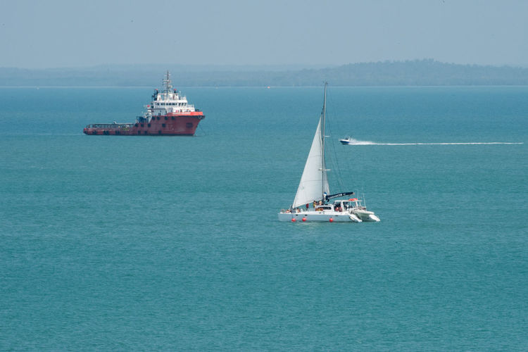 Darwin, Northern Territory, Australia-Sept. 9,2018: Three varying nautical vessels in the blue Timor Sea off the coast of Darwin, Australia Nautical Vessel Water Transportation Mode Of Transportation Sea Sailing Travel Waterfront Nature Day Beauty In Nature Sailboat Scenics - Nature Yacht Outdoors Luxury Yachting Darwin Timor Sea Boat Transportation Journey Adventure Exploration White Sail Catamaran Lifestyles Recreation  Vacations Outdoor Pursuit Recreational Boat Blue Turquoise Colored Northern Territory Australia Mast No People Ship Tranquil Scene Passenger Craft Motorboat Travel Destinations Travel Traveling Shipping  Barge Cargo Ship Container Ship Variation