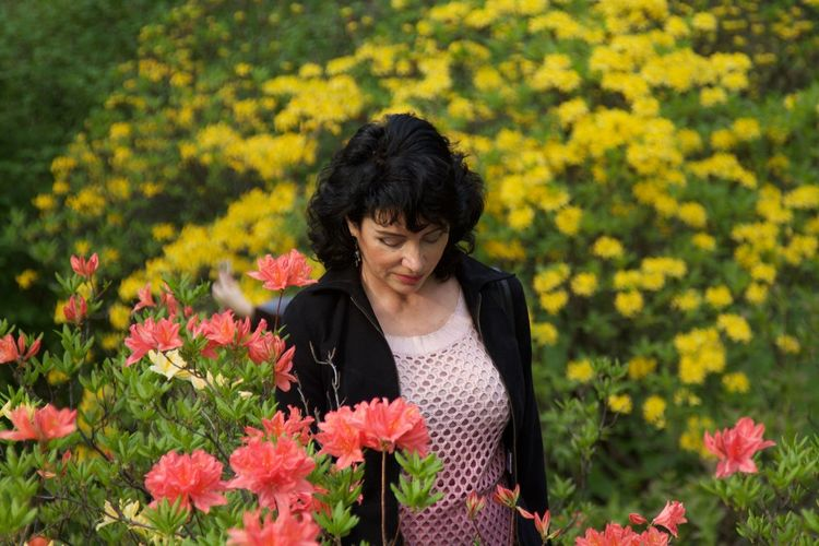 Woman Standing Amidst Flowers On Field