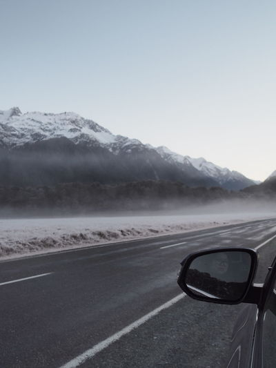 Car on road against snowcapped mountains