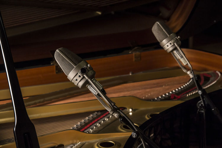Close-up of microphones by grand piano