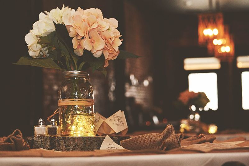 White flowers in jar on tree stump in wedding