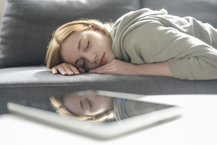 Close-up of woman lying on sofa reflecting in digital tablet