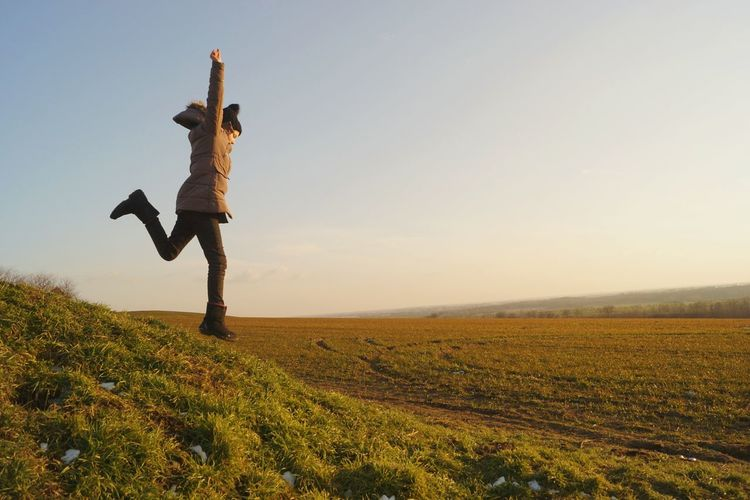 Side view of girl with arms raised running on grassy field against clear sky during sunset