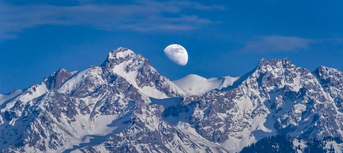 Moon Winter Snow Cold Temperature Blue Sky Beauty In Nature Nature No People Scenics - Nature Outdoors Tranquility Day Tranquil Scene Snowcapped Mountain Low Angle View Mountain White Color Cloud - Sky Environment