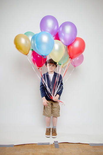 Boy holding colorful balloons against white background