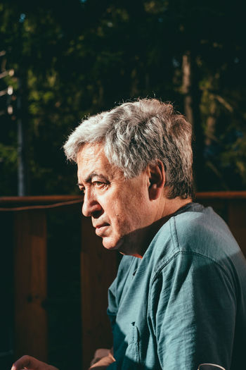 Profile View Of Thoughtful Senior Man Sitting Outdoors