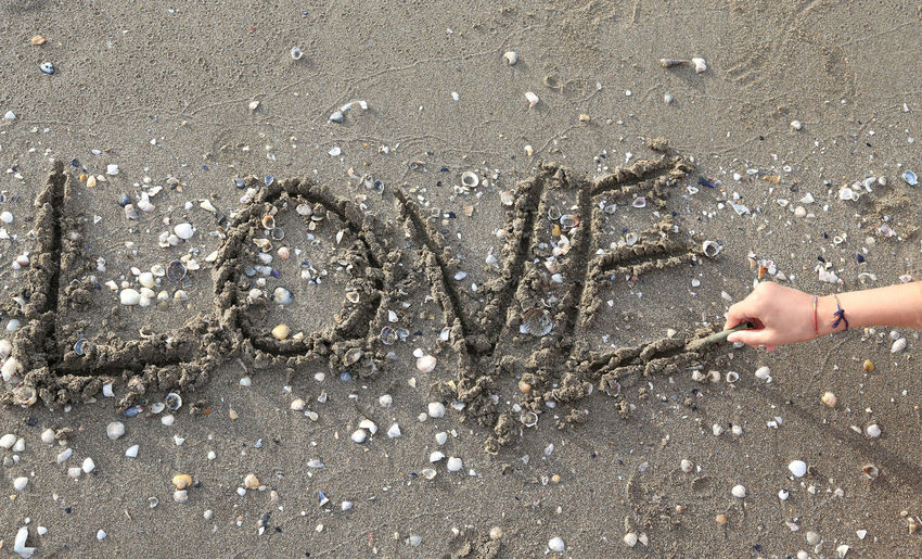 Cropped Hand Making Love Text On Sand At Beach