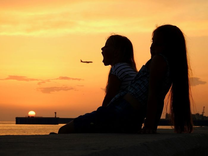 Silhouette Of Girls Sitting By Sea At Sunset