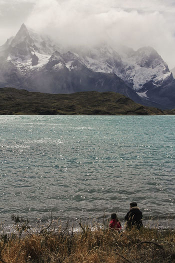 Mountain Water Beauty In Nature Real People Leisure Activity Scenics - Nature Nature Togetherness Lake Two People Tranquil Scene Lifestyles Day Tranquility Mountain Range People Rear View Non-urban Scene Outdoors Positive Emotion Snowcapped Mountain Couple - Relationship Father And Daughter