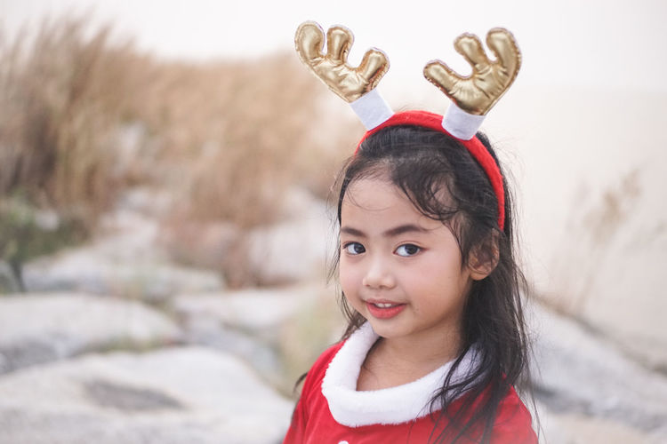 Little Santy/Reindeer on Stone dam at sea side.Little Girl in Santa Claus dress with Reindeer Headband. Santy  Santa Santa Claus Reindeer Stone Dam Sea Sea Side Thailand Winter Fashion Girl Little Girl Kid Asian  One Person Child Childhood Portrait Smiling Girls Looking At Camera Females Headshot Emotion Focus On Foreground Cute Innocence Front View Lifestyles Women Happiness Warm Clothing Hairstyle