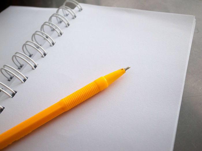 High angle view of yellow pen on blank spiral note pad