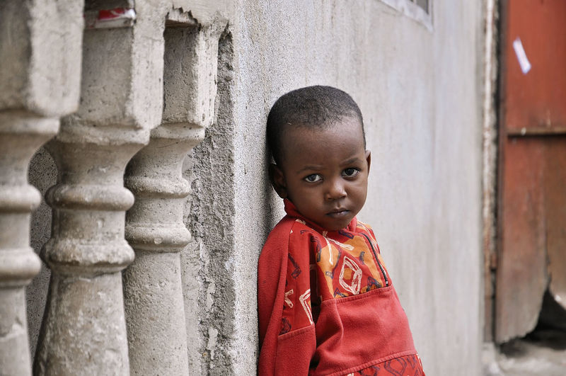 Boy Childhood Innocence Standing Wall - Building Feature Red Jacket Child Architecture Portrait One Person Offspring Day Cute Built Structure Architectural Column Emotion Looking At Camera Lifestyles Outdoors Human Face Emotional Contemplation African Child My Best Photo EyeEm Best Shots Eyeem Children Children