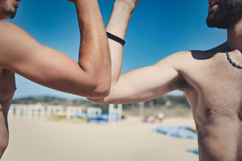 Midsection of shirtless men following social distancing with elbow bump at beach