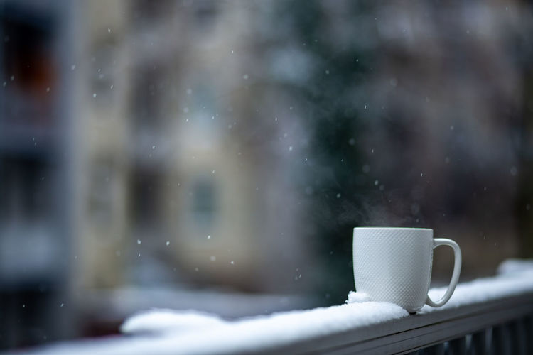 Close-up of coffee cup on window during winter
